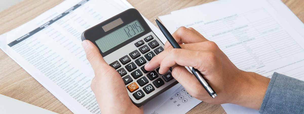 Unrecognizable businessman using calculator to find out income and outcome. He counting company finances. Male hands with pen pushing button at desk. Investment or paperwork concept
